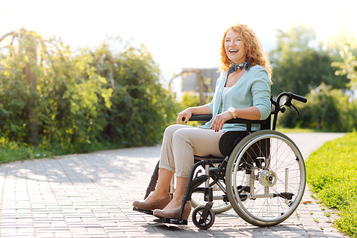 Despite difficulties. Positive senior wheelchaired woman laughing and sitting in the wheelchair while resting in the park